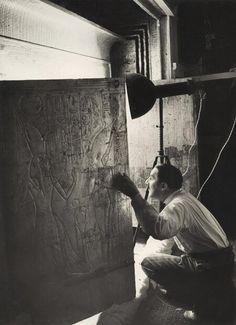 Howard Carter looking through the Open Doors of Tutankhamun's Second Shrine, 1924. Taken by Harry Burton.