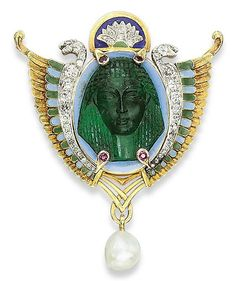AN EGYPTIAN REVIVAL EMERALD, ENAMEL AND DIAMOND BROOCH - Of shield shape, centering upon an emerald cameo depicting a facing Ancient Egyptian head, surrounded by two diamond-set winged snakes applied with blue and green enamel, suspending a baroque-shaped pearl, late 19th Century.