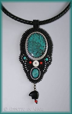 The pendant consists of two turquoise cabochons that are bezeled with silver plated Miyuki delica beads. It is further embellished with black and silver plated Miyuki seed beads, a bone bead, turquoise beads, red coral beads, sterling silver beads, and a little black onyx zuni bear.