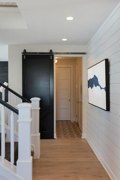 This black sliding door is a great addition to a white mudroom with shiplap walls.