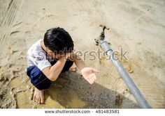 Close up thin focus on old faucet that Young Asian boy waiting for water on hot and dry empty land. Water shortage and drought concept.