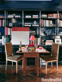 Miles Redd designed the ebonized wood and sterling bookshelf, where a colorblock painting by Leora Armstrong hangs. When they're alone, the owners of this Manhattan apartment dine at this carved flip-top game table from Agostino Antiques.   - HouseBeautiful.com