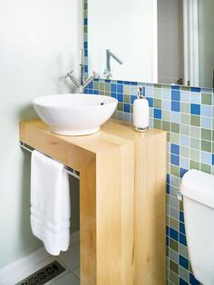 An L-shape vanity that butts up against a wall maximizes limited floor space, while a bowl-shape vessel sink and a corner-mount faucet free up counter space for soap and toiletries. When choosing a clean-lined unit with an open area below, a simple towel rack can help hide plumbing fixtures or storage baskets.