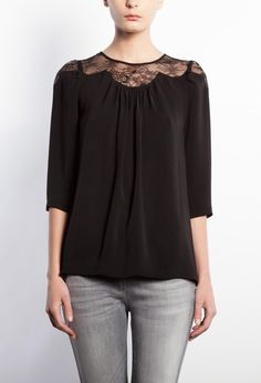 Flared blouse with elbow-length sleeves, round neckline, lace inset at the neckline and at the top of the shoulders, gathers at the front, row of buttons at the back.
