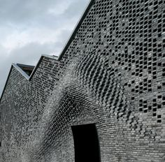 Archi-Union Architects, which previously completed a nearby contemporary arts centre featuring curved concrete walls, developed this undulating brick design to combine traditional materials with contemporary robotic manufacture.