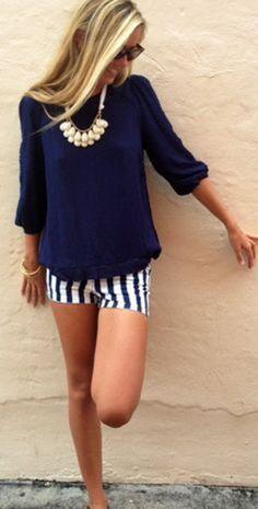 Den Look kaufen: https://lookastic.de/damenmode/wie-kombinieren/langarmshirt-dunkelblaues-shorts-weisse-und-dunkelblaue-sonnenbrille-dunkelbraune-halskette-hellbeige/2780 — Dunkelbraune Sonnenbrille — Hellbeige Halskette — Dunkelblaues Langarmshirt — Weiße und dunkelblaue vertikal gestreifte Shorts