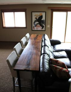 bar table and seating behind a couch--like this idea for a basement.