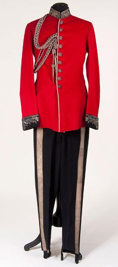 A BRITISH VICTORIAN MILITARY DRESS TUNIC AND TROUSERS, circa 1890.  Red wool with black collar and cuffs heavily embroidered with silver bullion oak leaf motifs and Tudor rose collar badges, and white piping.  Silvered buttons embossed with Queens crown.  Together with a bullion and red mixed cord aiguillette.  Complete with black wool trousers with brocade stripes.