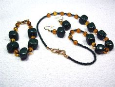 Completely original jewelry set. These beautiful dark forest green beads were handmade by me in my home studio from polymer clay. They have a satin finish. I put them together with purchased amber glass round beads and glass dark green seed beads. Both the necklace and bracelet are finished screw crimps, wire guards and gold tone hooks. Class all the way. The earrings have hypoallergenic gold tone ear wires. These are truly One of a Kind pieces. Please zoom in to see the details and…