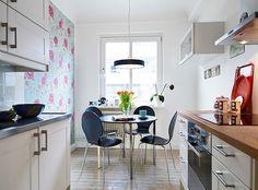 Un apartamento nórdico en tonos fucsia. Otro empapelado super femenino en la cocina.