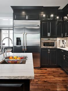Black cabinets with white granite counters and distressed hardwood floors, stainless appliances Coastal Va Magazine's Best Kitchen & Bathroom Remodeler #dogoodwork www.jimhicks.com