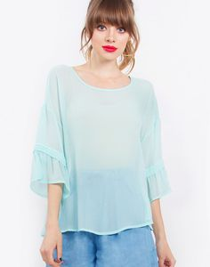 Loose and flowy mint sheer top with wide sleeves. Features a trim around the sleeves.