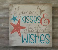 This wood sign features the words Mermaid Kisses and Starfish wishes painted in deep coral, turquoise and light tan all on a off white
