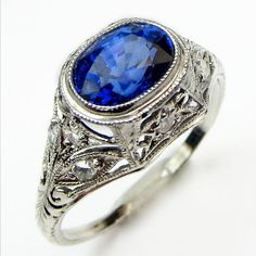 Lacy Blue: A stunning Edwardian confection featuring a vibrant oval sapphire bezel set above a gracefully domed mounting liberally covered with lacy floral filigree and a sprinkling of fiery diamonds.  Ca 1915. Maloys.com