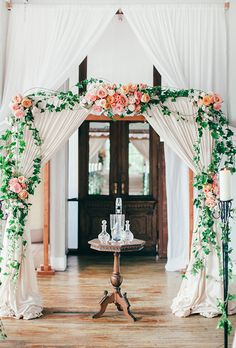 Brides.com: . Soft white curtains make the perfect backdrop for this lush wedding altar crawling with green ivy and lush pink florals.