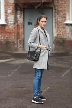 Lifestyle fashion portrait of beautiful young brunette woman in grey coat with black leather bag posing on street cloudy day — стоковое изображение #117238190