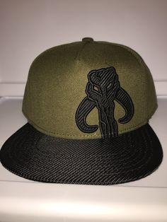 Bioworld snapback Warriors of Mandalore brim & boba fett symbol in textured black with dark green cap. Spencer's exclusive