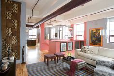Open Concept Loft - Living Room - Family Room - View into Kitchen and Dining Area - Drum Pendant Light Fixture - Asian Art - African American Art - Tribal Art - Modern Art - Antiques - Industiral Contemporary Loft - Hardwood Floors - Striped Rug - Leather Ottoman - Upholstered Stools - Coral - Burgandy - Gray