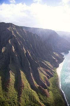 Na Pali Coast in Kauai, Hawaii ハワイ・カウアイ島の北西部に位置するナ・パリ海岸の斜面。数百万年前の火山の噴火で島が形成されたが、今は火山活動はなく、侵食が継続している。斜面の上での流水による侵食と、斜面基部での波による侵食が複合してできた、険しく印象的な地形。 https://twitter.com/ogugeo/status/332986992944103424