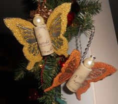 "Wine cork ornaments. One pinner suggested doing it ""with feather wings and dangles for legs. No head. Cork covered in book page or sheet music."""