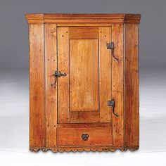 Love this cupboard!!! Sold For $2,900       Pennsylvania Hanging Cupboard      Pennsylvania, ca 1740s, a hanging cupboard in walnut with chestnut secondary, with moulded cornice over a paneled door with wrought iron rat tail hinges, over one thumb moulded drawer, the base with scalloped edge, on a later stand; ht. 75.5, wd. 34, dp.      Provenance: Property of Donald Baird, PhD