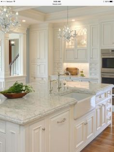 [Beautiful cabinetry and countertop.] A little too traditional and never any chandeliers...but yes to white cabinets and faux marble quartz countertops