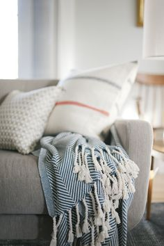Curbly Family Living Room - Resources: Flannel Pillow: Fairbault Wool Pillow Cover - Ticking Stripe from West Elm Ikat Pillows, Wool Pillows, Home Interior Design, Interior Decorating, Ticking Stripe, Pillow Covers, West Elm, Blanket, Living Room