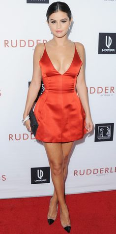 LOOK of the DAY OCTOBER 8, 2014 Selena Gomez Selena Gomez was smokin' hot at the Rudderless screening in a plunging, micro-short red satin Dior dress, accessorizing with diamond drop earrings, a stack of bangles, a dark gray envelope clutch, and translucent Manolo Blahnik cap-toe pumps.