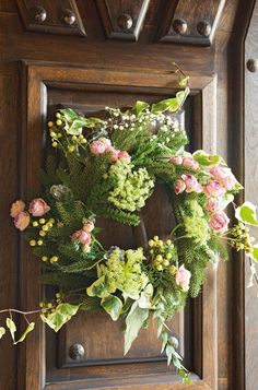 Beautiful evergreen wreath adorned with pastel pink roses and babies breath