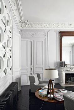 Poltrona Basil di Christophe Delcourt con rivestimento in tessuto grigio. La lampada da tavolo, il coffee table danese e l'opera tridimensionale alla parete provengono dal Marché Paul Bert.