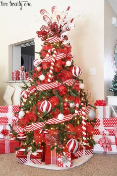 Red and white Christmas tree with candy cane striped ribbon, red mesh ribbon, ornaments, and red and white wrapped Christmas gifts. Elf Christmas Decorations, Candy Cane Christmas Tree, White Christmas Trees, Beautiful Christmas Trees, Christmas Tree Toppers, Christmas Tree And Gifts, Christmas Tree Mesh Ribbon, Christmas Christmas, Christmas Mantles