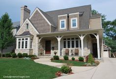 Stone Front porch with Cedar Siding and wood door entry Rocking chairs on porch professionally landscaped