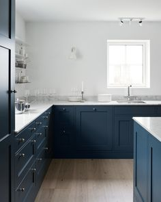 Nordic Shaker kitchen - Nordiska Kök. A modern Shaker kitchen built in classic style. The dark grey-blue color together with the bare white walls and industrial touches give the kitchen a modern tone. For more kitchen inspiration visit www.nordiskakok.se #kitchen #bespokekitchen #shakerkitchen #shaker #interior #architect #grey #limestone #white #framekitchen #minimalism #minimalistic #wood #kitchendesign #kitchenideas #greykitchen #design #designtrends #beautifulkitchens