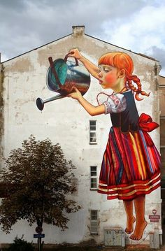 Little girl watering a tree