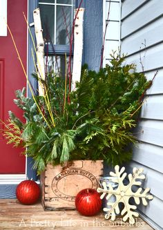 Fresh Outdoor Christmas Planters with evergreens, sticks & birch branches. Post also includes an evergreen wreath, and DIY outdoor Christmas trees using tomato cages!