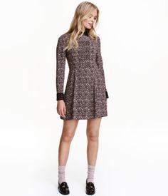 Sort/Rosablomstret. Kort kjole i crepet, vævet kvalitet med krave og manchetter i blonde. Kjolen har læg foroven og lange ærmer. Er skåret i taljen med