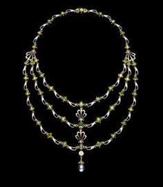 Gold, black and white enamel and demantoid garnet necklace, hung with an oriental grey pearl. Anthemion (honeysuckle) motifs clasp the three rows at the front of the necklace and fasten them at the sides to the single row at the back. Throughout, graduated damantoid garnets in beaded gold settings alternate with openwork links enamelled black and white. Signed C & AG, for Carlo and Arthur Giuliano, on the back of the clasp behind. English, c. 1900.