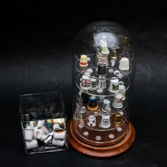 A collection of thimbles with display case. This selection features thirty-five thimbles and one round display case with a walnut tone base, four shelves, and a domed glass enclosure. Highlights include an owl shaped thimble in cobalt blue and emerald green tones, a sky blue thimble with an ivory tone Madonna and Child relief, a pearlescent souvenir thimble from Switzerland, and more.
