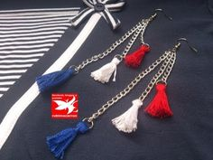 Pendientes con cadenas y ponpones de hilo de bordar en azul marino, rojo y blanco .