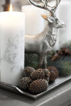 Silver stag, pine cones and silver-dusted white candle