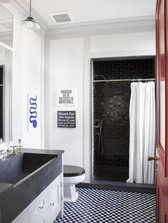 Contemporary boy's bedroom features a shower nook filled with glossy black brick tiles and a black shower floor finished with a white shower curtain.