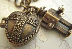 Steampunk Robot Charm Bracelet Tin Man & Heart Locket Antiqued Brass Bronze Rustic Finish Costume Fashion Jewelry. $15.00, via Etsy.