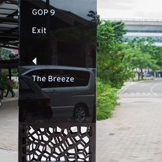 Vehicular directional signage in black backpainted glass, brushed stainless steel and white sticker content.