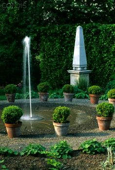Fountain surrounded by buxus sempervirens in pots with a stone Obelisk behind. Arrow Cottage, Herefordshire