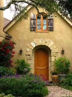 stucco house with beautiful window and door details and a lush garden.