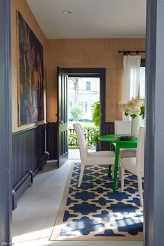 A vintage-inspired dining room contains a pop of color, shown in the green table.