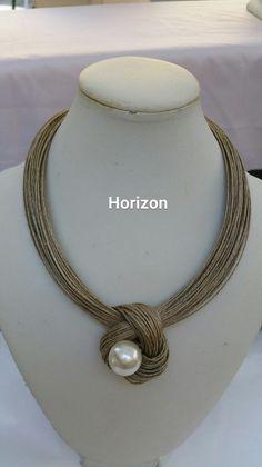 collier en fil de lin agrementé d'une perle nacrée écru au centre d'un nid de lin