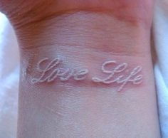 Ambigram tat on wrist in white ink (Derrek/Darren)