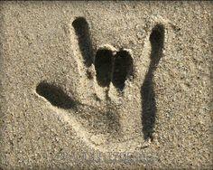 ILY handshape on the sand beach