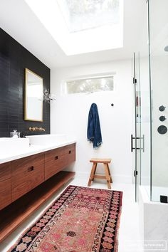 Modern bathroom with pink kilim rug, black tile walls and wood cabinets / designed by Amber Lewis of Amber Interiors